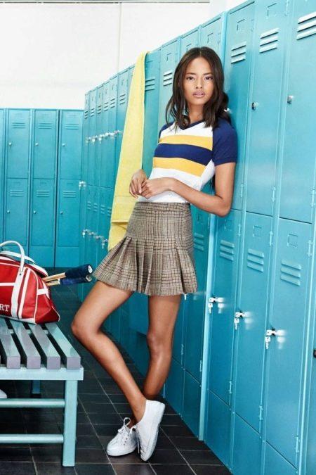 Бежевая мини-юбка в клетку отлично сочетается с желто-синей футболкой в  широкую полоску, спортивный образ завершают не привлекающие к себе внимание  белые ... ed244671b01